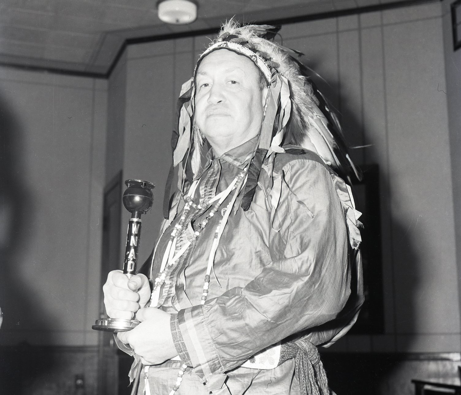 photo of Chief Don Whistler4)Don Whistler, Chief of the Sac and Fox tribe, and creator of Indians for Indians, in the WNAD studio. OU Photographic Service #16339, University Archives, OU Libraries Western History Collections.