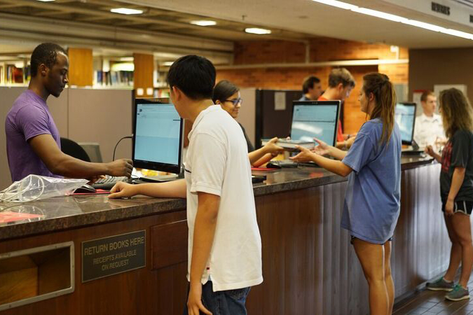 Students checking items out at the main circulation desk