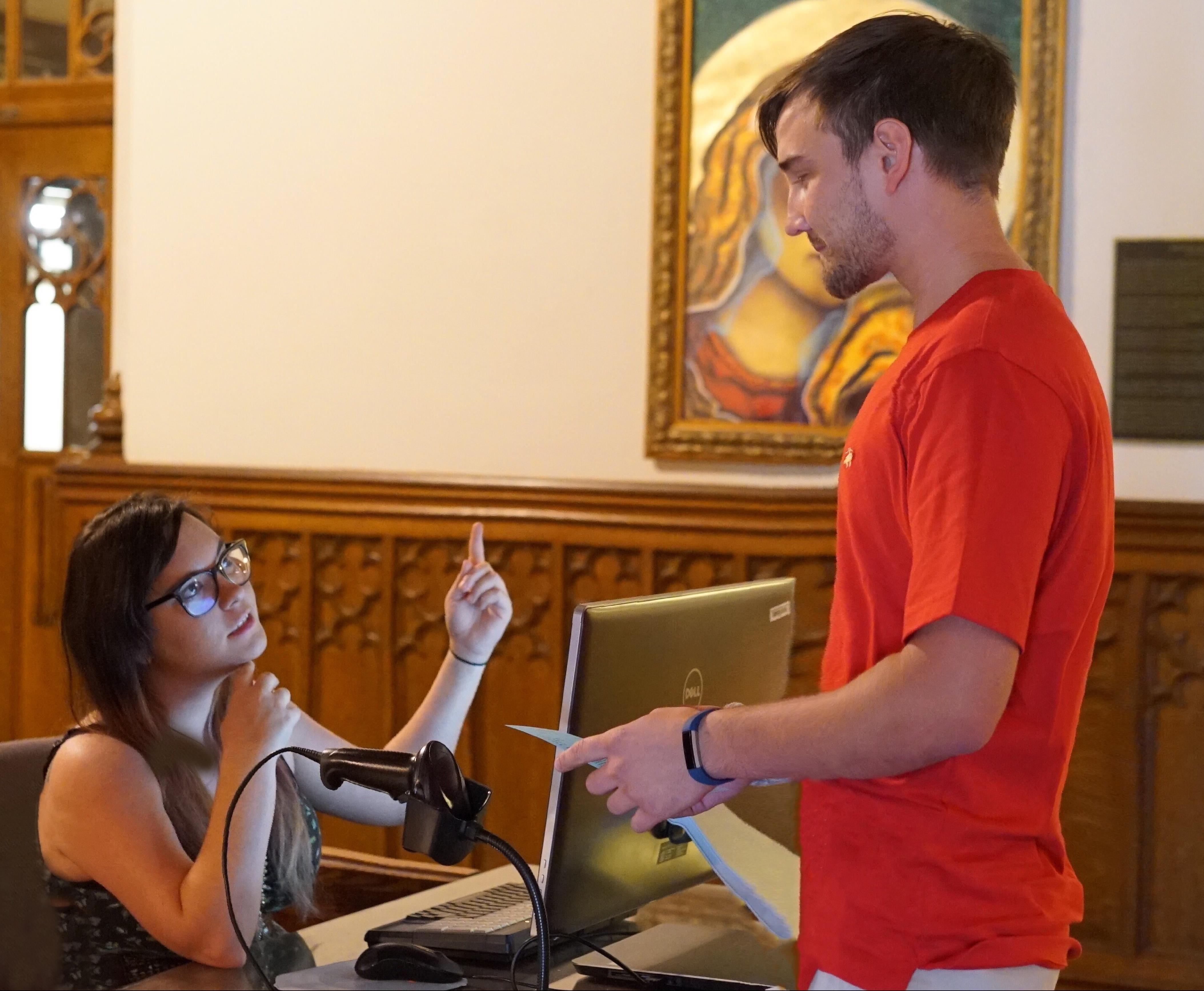A student asking for directions at the South Gate circulation desk