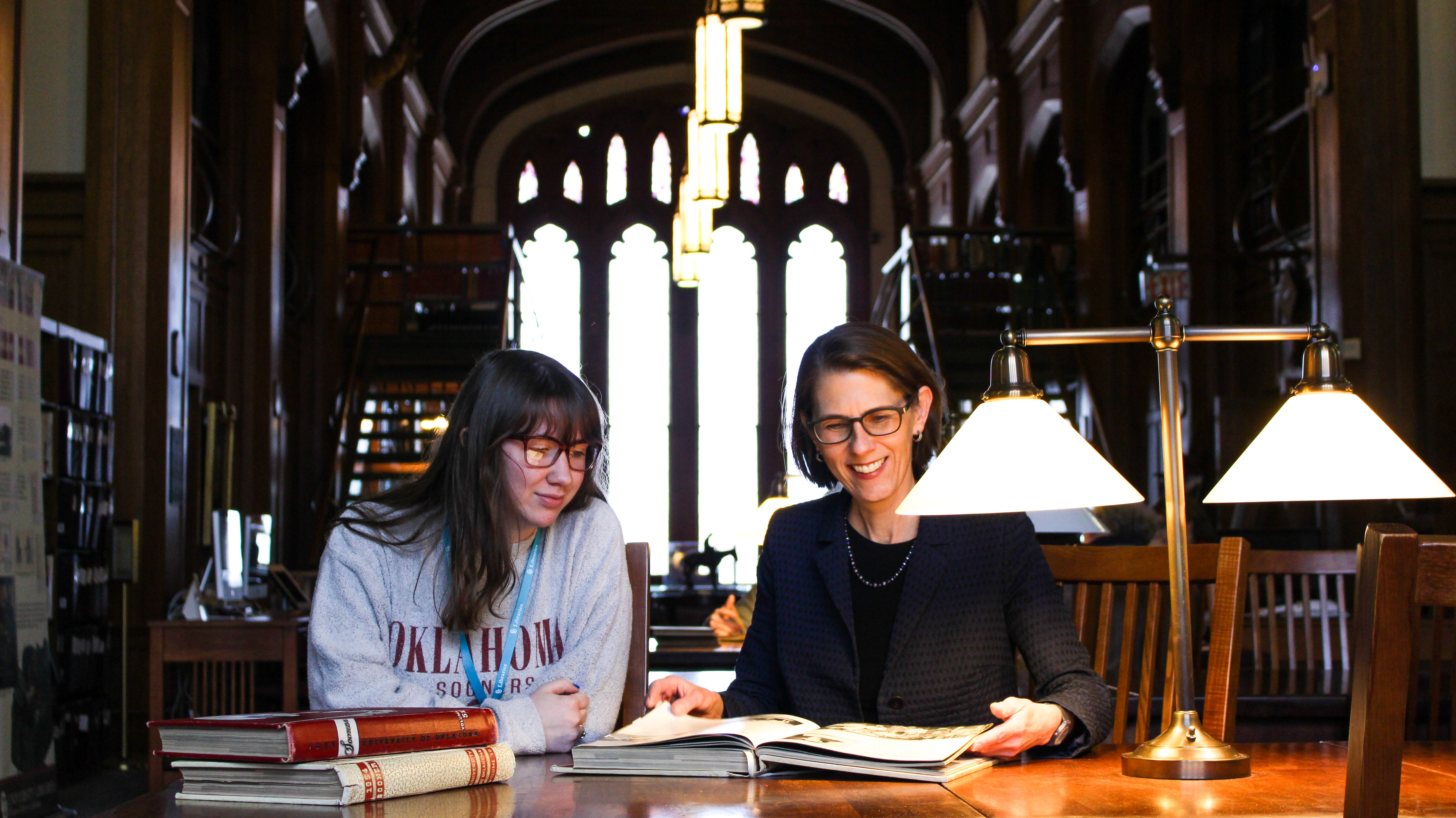 OU Libraries associate dean for special collections Bridget Burke with OU freshman Maddie Fitter in the Western History Collections Reading Room, Monnet Hall. OU Libraries' special collections will welcome seven research fellows this summer.