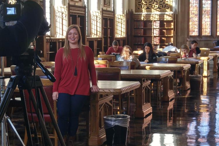 A photo of a student being filmed in the great reading room